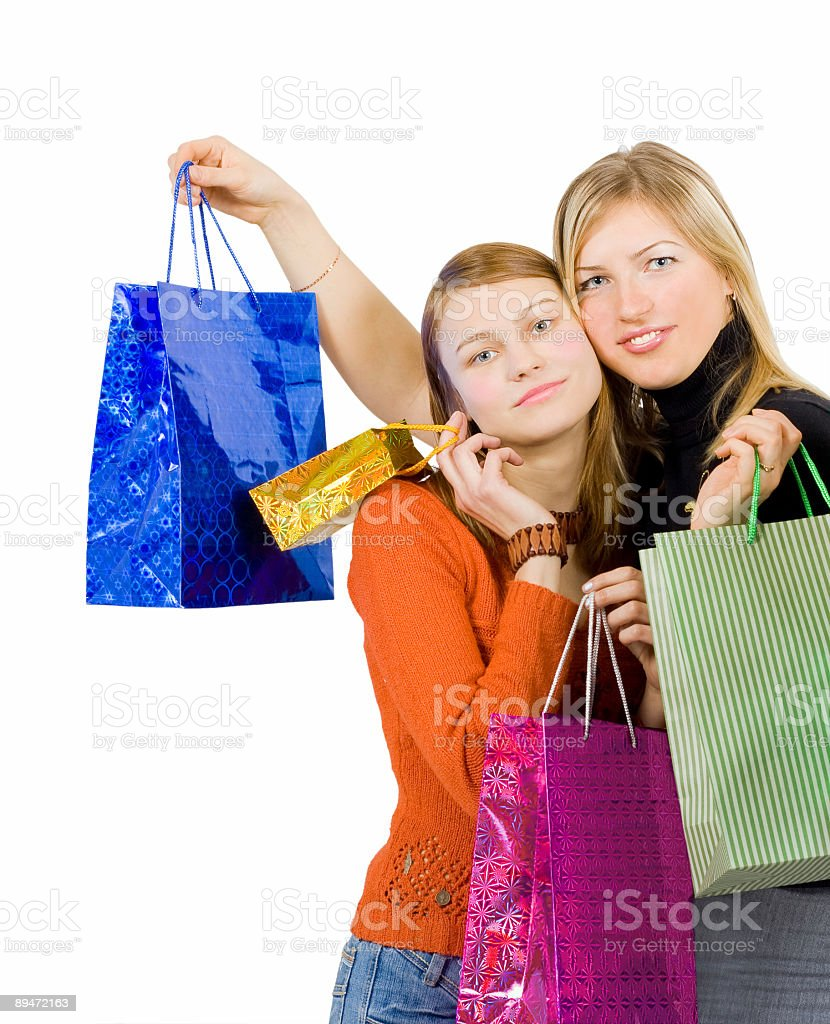 two girlfriends hugging having made a shopping run royalty-free stock photo