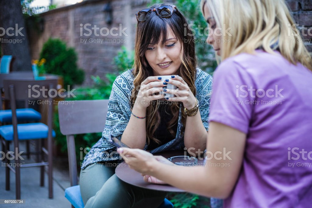 Two girlfriends in cafe looking in smart phone stock photo