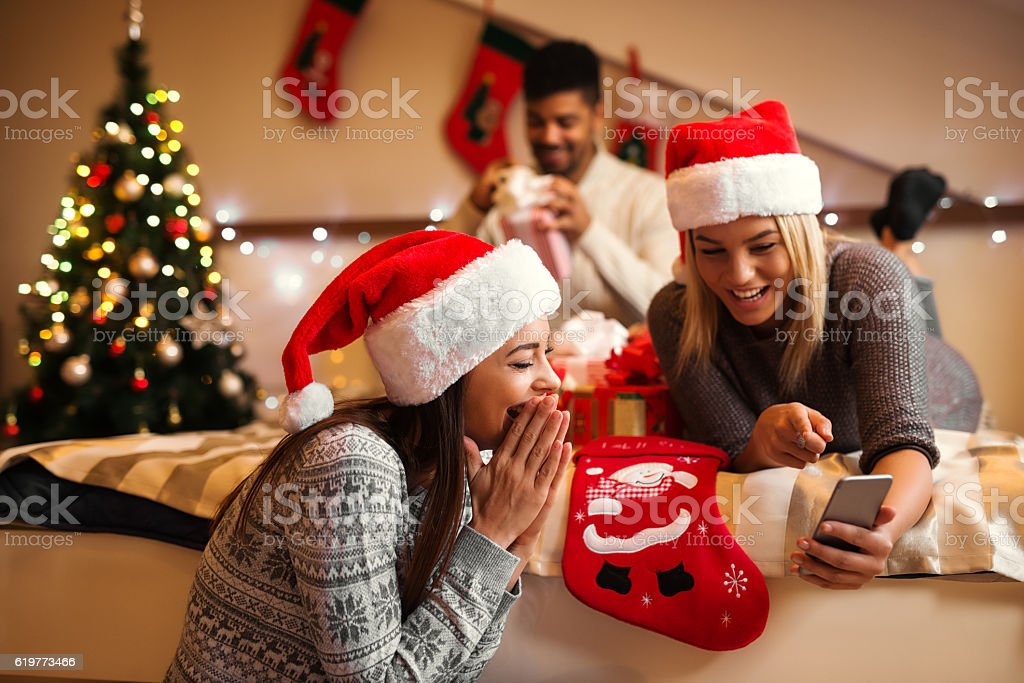 Two girlfriends laughing and looking at smart phone. stock photo