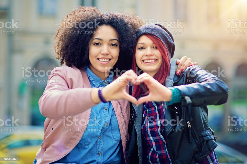 Two girlfriends making heart with their hands on the street - Photo