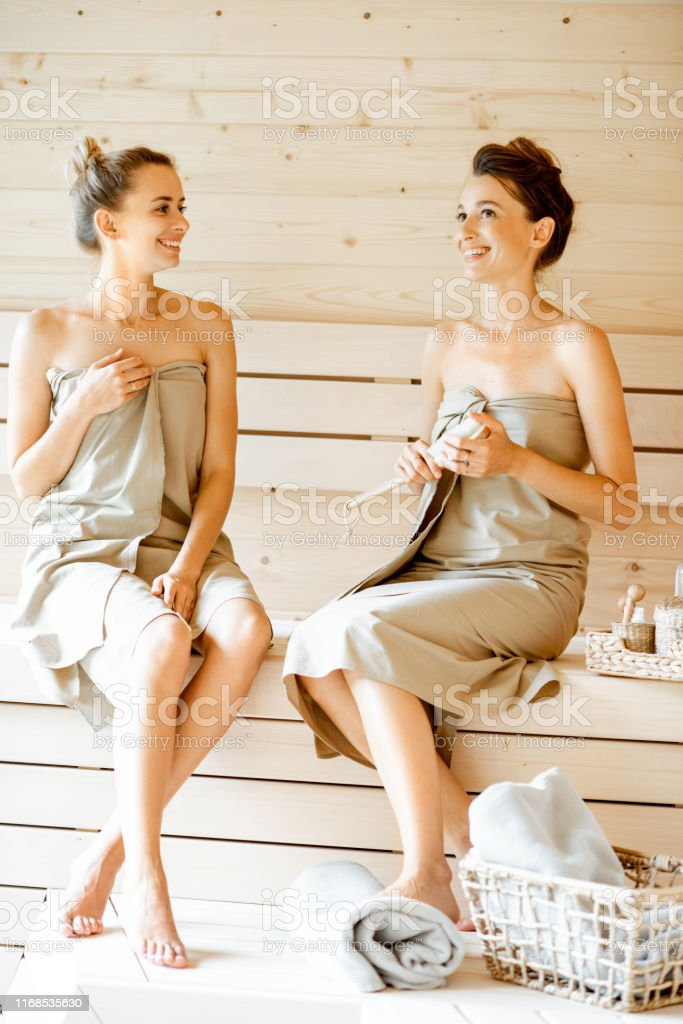 Two young girlfriends relaxing in the sauna, sitting together and...