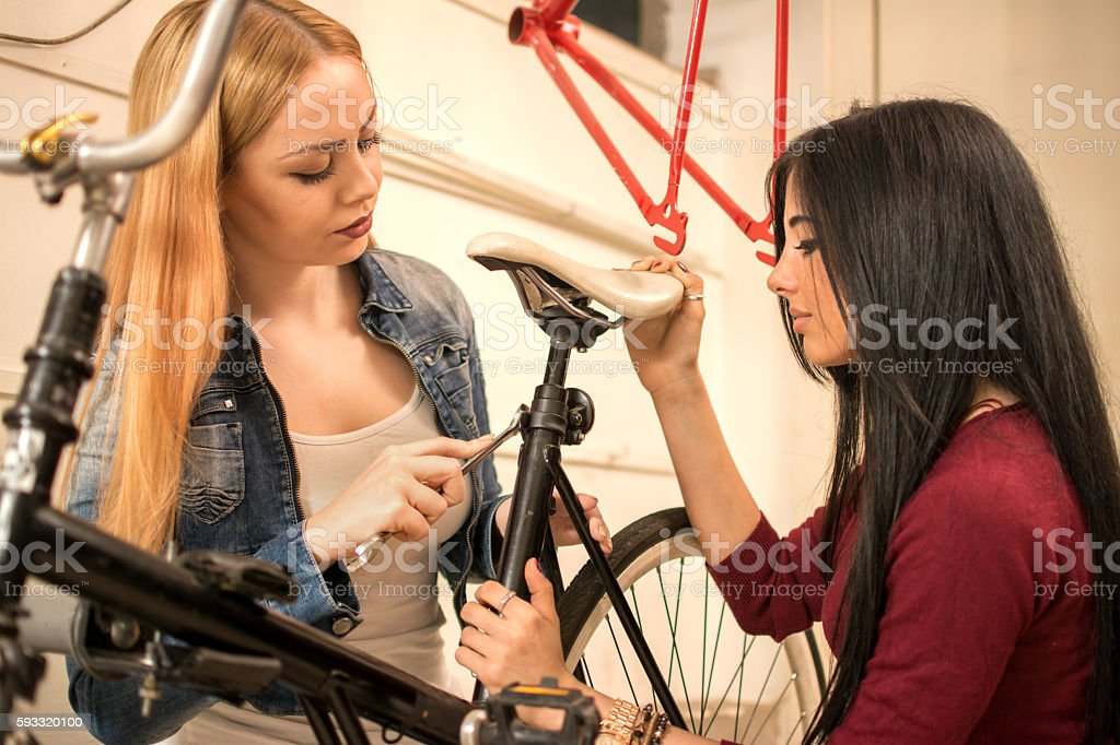 Two girlfriends repairing bicycle in garage. stock photo
