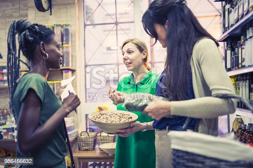 Two girlfriends, African and Caucasian ethnicity, shopping in grocery store, talking to merchandiser