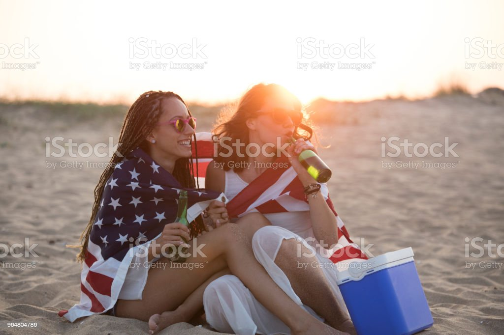 Two girlfriends sitting on beach and drinking beer royalty-free stock photo