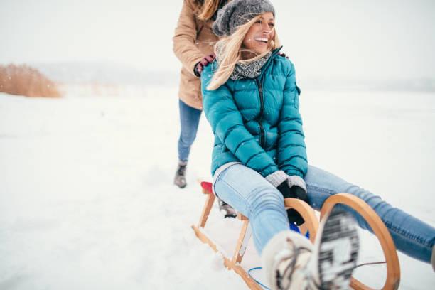 zwei freundinnen in einem wintertag rodeln - gute winterjacken stock-fotos und bilder