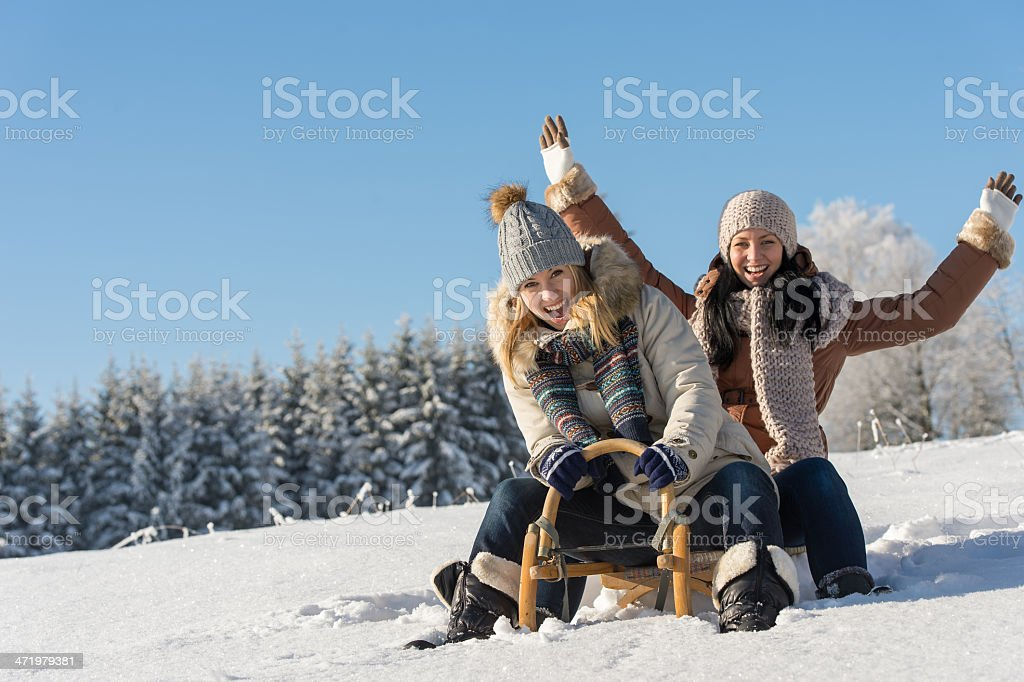Two girlfriends snow sledge downhill in wintertime stock photo