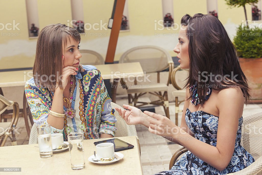 Two girlfriends talking in cafe stock photo