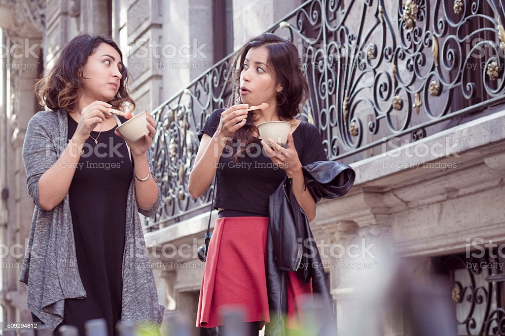 Two girlfriends walking and eating an ice cream stock photo
