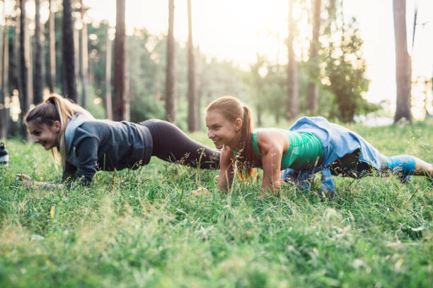 two girlfriends working out outdoors doing plank exercise on grass - peso mosca foto e immagini stock