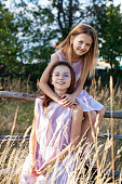 two girls 8-10 age and 12-14 age are sitting on the fence outdoors