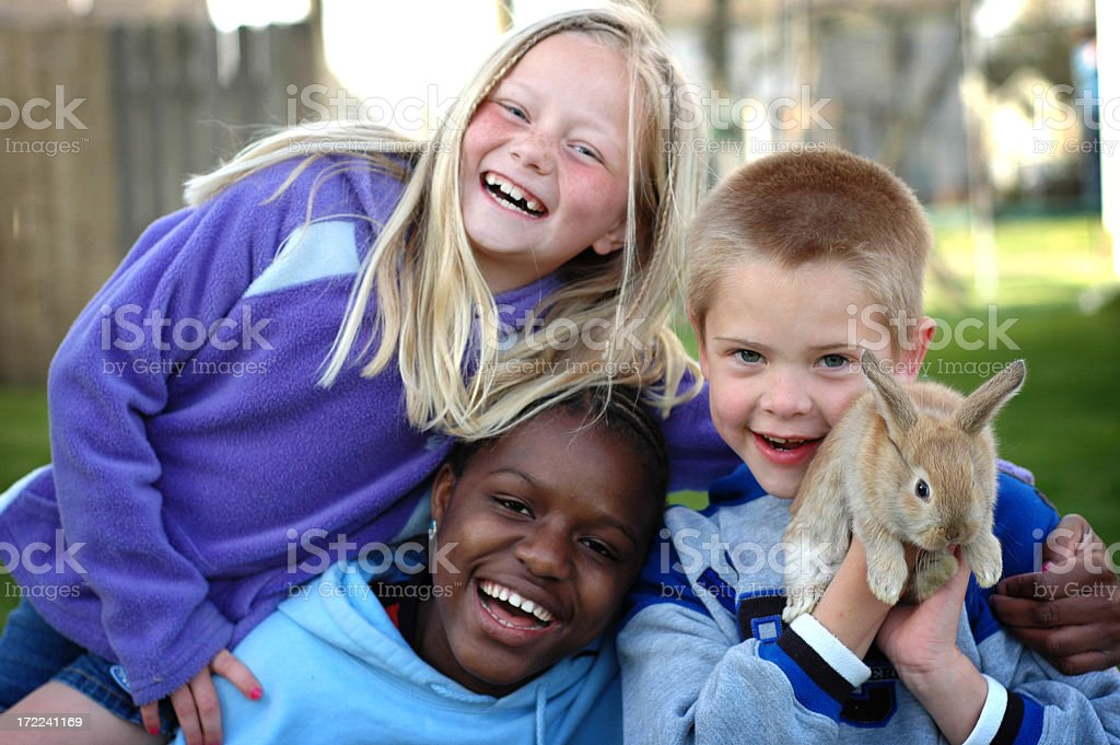 Two Girls and a Boy Laughing Together Outside with Bunny royalty-free stock photo