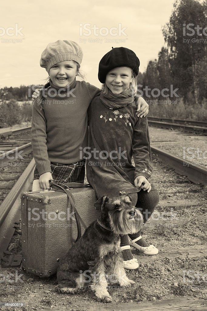 Two girls and a dog go by rail stock photo