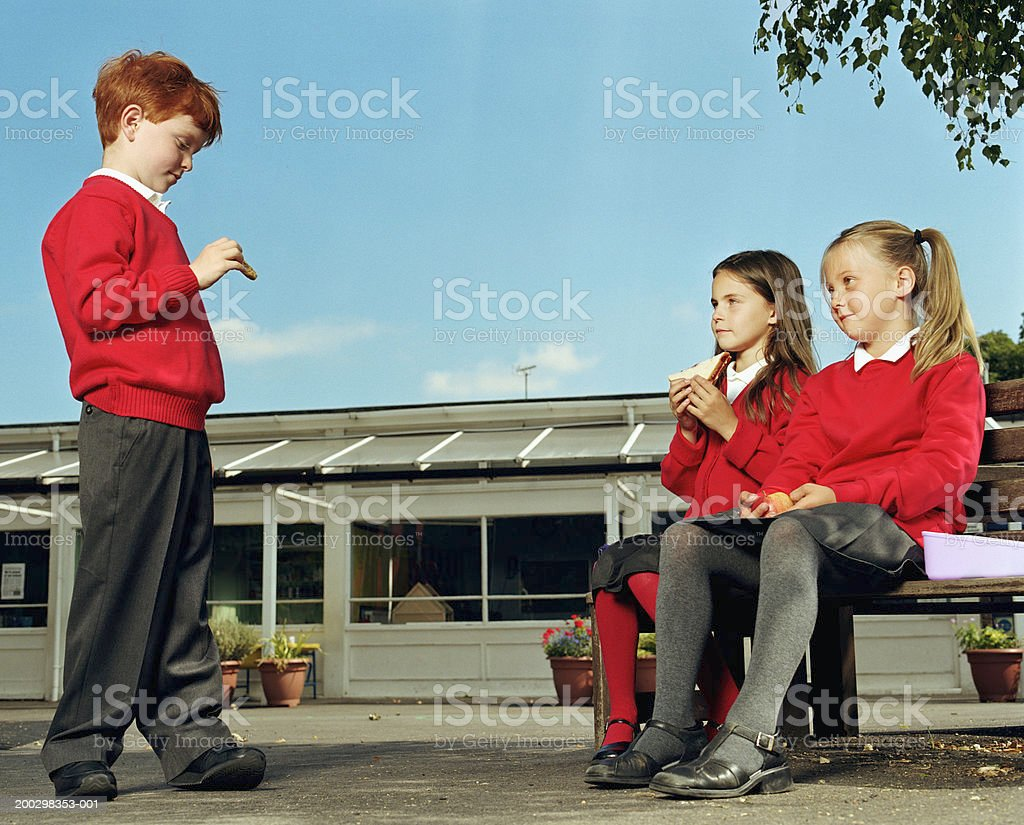 Two girls (6-8) and boy (5-7) eating lunch in playground royalty-free stock photo