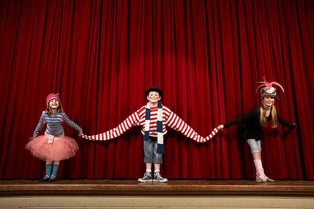 Two girls and boy (6-10) in costume taking bow on stage, smiling stock photo