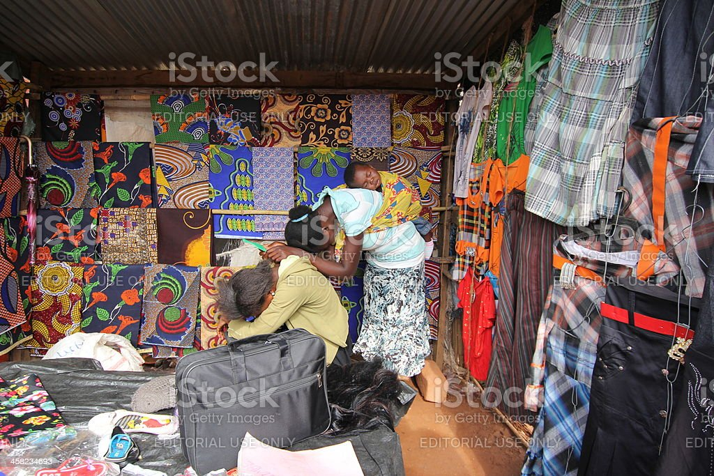 Two Girls and one Baby in an African Textiles Shop stock photo