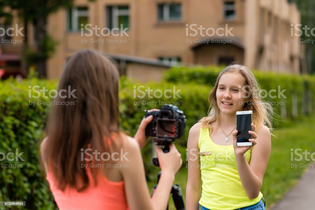 Two girls are bloggers. Young journalists. Describes advantages of phone. Make a broadcast on the Internet. Record vlog and blog subscribers. Record video lesson for Internet. Use camera with tripod. stock photo