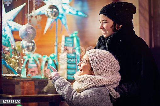 Two girls are looking candy store window at Christmas