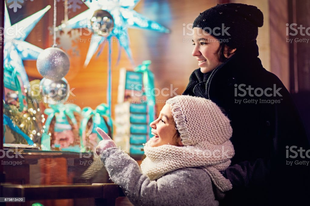 Two girls are looking candy store window at Christmas stock photo