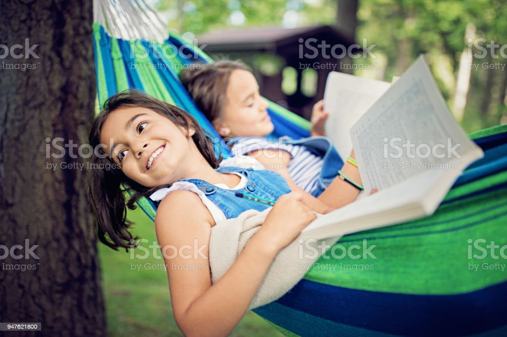Two girls are lying down in the hammock and reading books stock photo