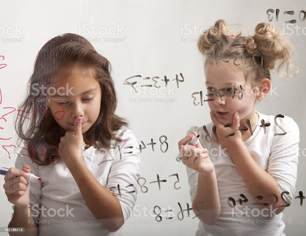 Two girls are making their mathematic assignment royalty-free stock photo