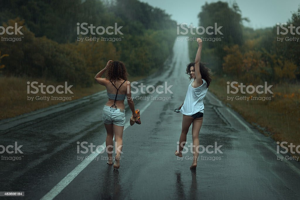Two girls are on roadway in the rain. stock photo