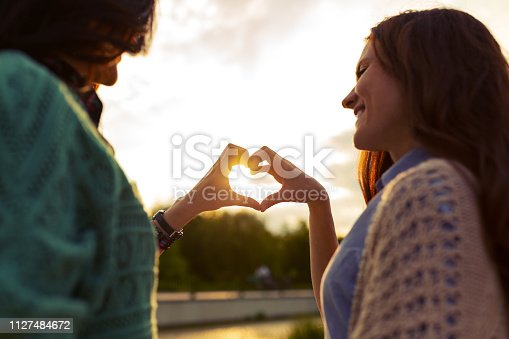 Two girls are showing heart from hands at sunset, symbol of connection, with sunlight in the middle. Friends forever.