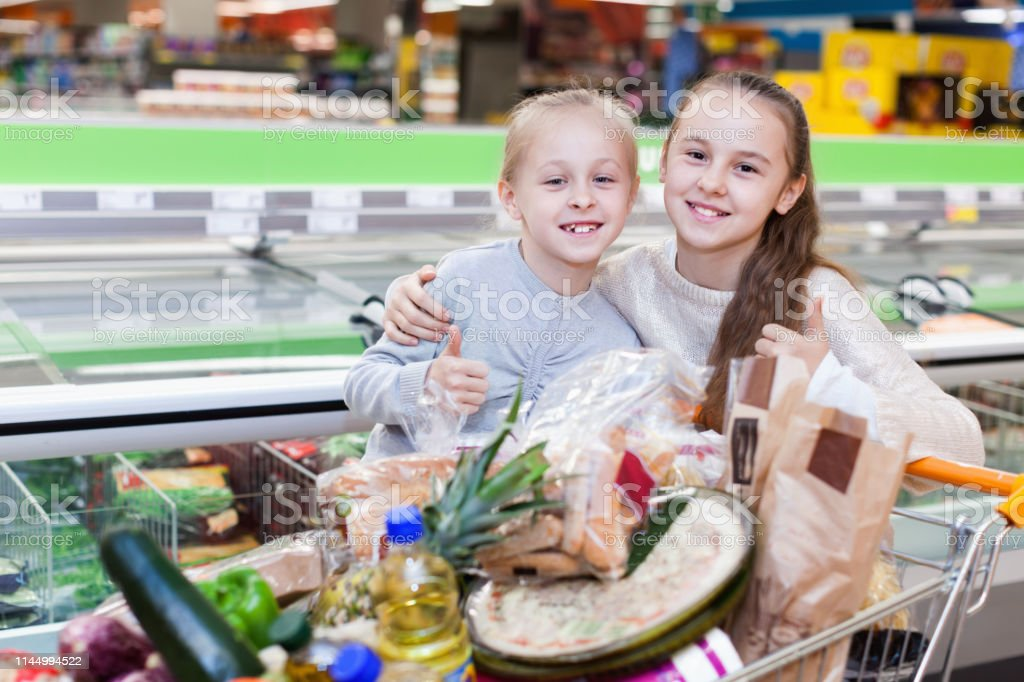 Two cheerful positive girls are standing with cart with products in...
