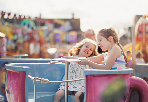 Two happy little girls are spinning around on a tea cup ride at an amusement park