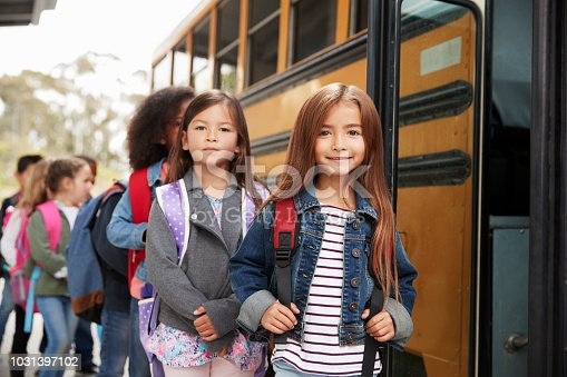 1031397608 istock photo Two girls at the front of the elementary school bus queue 1031397102