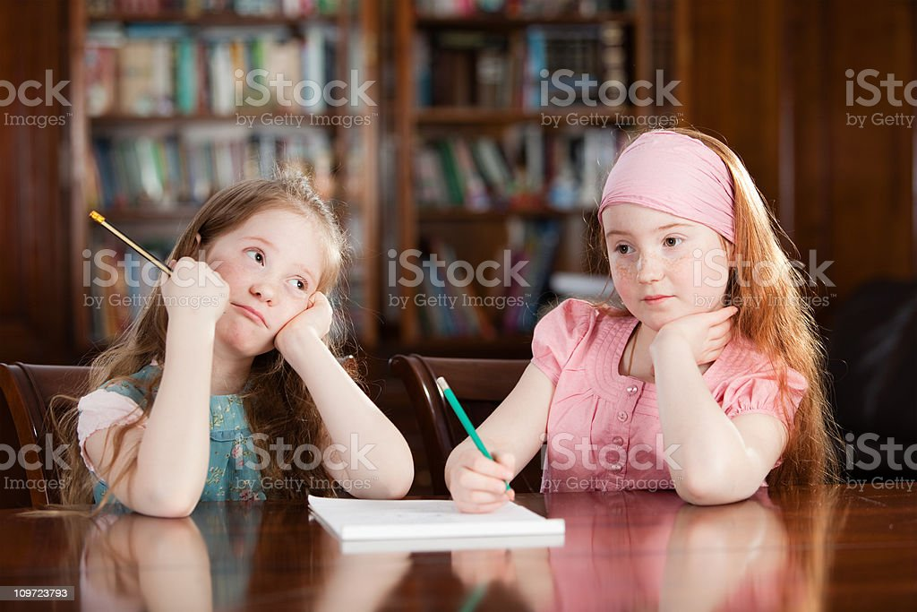 Two girls at the table doing their homework royalty-free stock photo