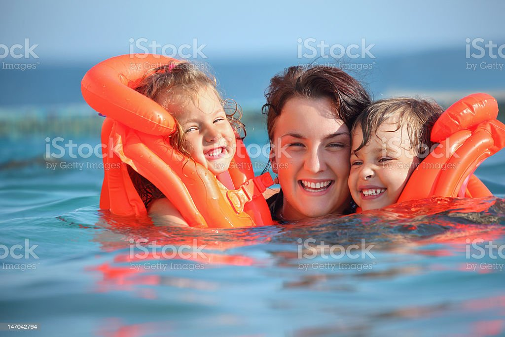 Two girls bathing with young woman in pool stock photo