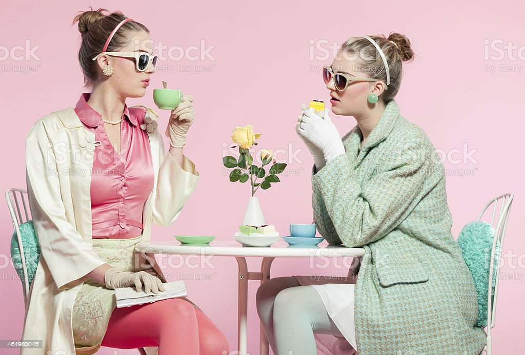 Two girls blonde hair fifties fashion style drinking tea. stock photo