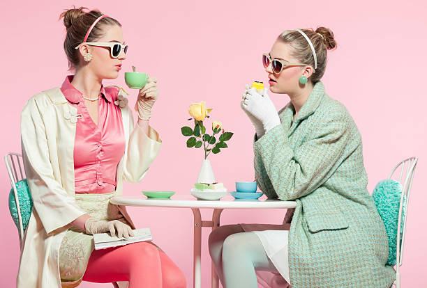 zwei mädchen blonde haare fünfziger mode stil trinkt tee. - make up torte stock-fotos und bilder