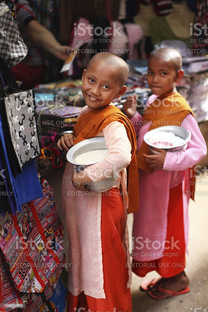 Two girls, buddhist nuns holding alms bowls with rice, Burma royalty-free stock photo