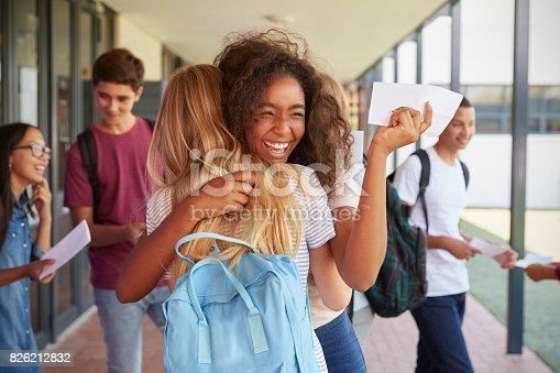 istock Two girls celebrating exam results in school corridor 826212832