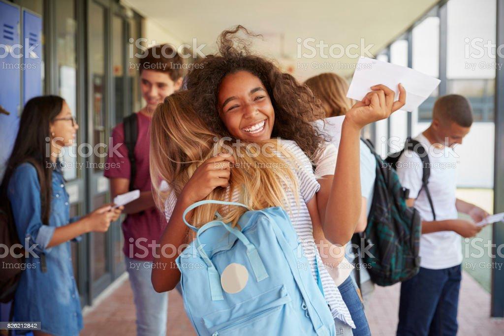 Two girls celebrating exam results in school corridor
