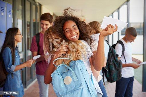 istock Two girls celebrating exam results in school corridor 826212842