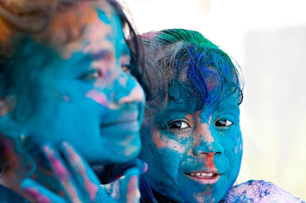 zwei mädchen feiert holi - indische gesichtsfarben stock-fotos und bilder