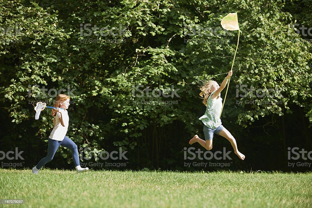 Two Girls Chasing Butterflies In Summer Field stock photo