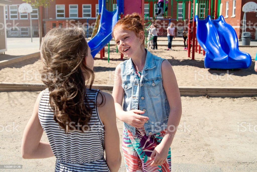 Two girls chatting in school playground at recess.. stock photo