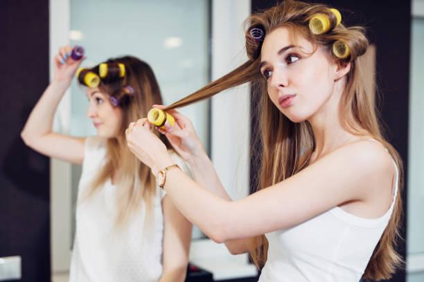 Zwei Mädchen curling ihre Haare mit Rollen in einem Raum – Foto