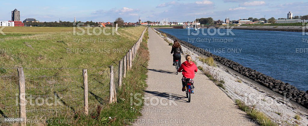 Two girls cycling along the harbour entrance of Zierikzee stock photo