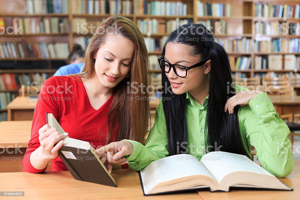 Two girls discussing a book at library stock photo