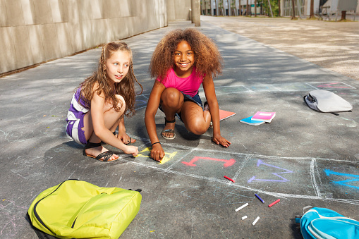 istock Two girls draw hopscotch game on the asphalt 831386286