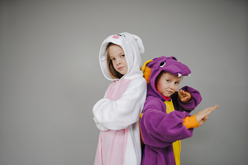 two girls dressed as rabbit and dragon posing in front of grey background