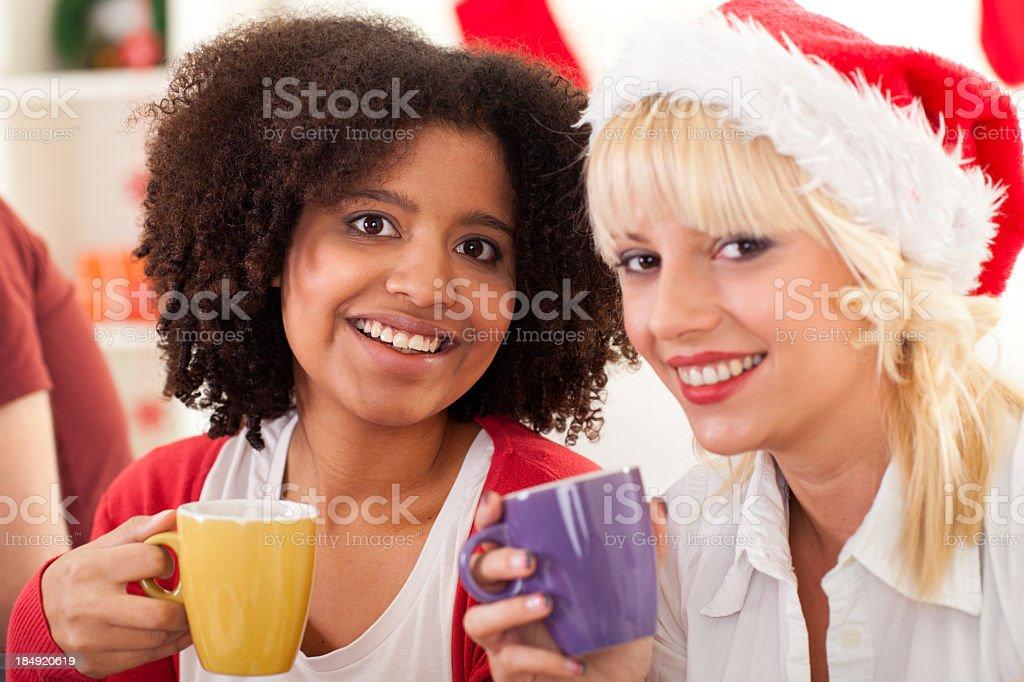 Two girls drinking coffee, enjoying Christmas holidays royalty-free stock photo
