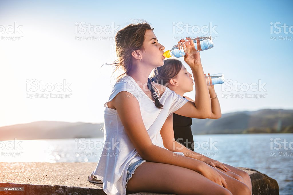 Two girls drinking water and sitting on dock stock photo