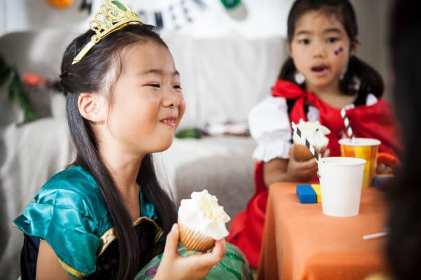 zwei mädchen essen muffins auf einer halloweenparty. - prinzessinnen torte stock-fotos und bilder
