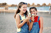 Two happy girls eating ice cream on the beach