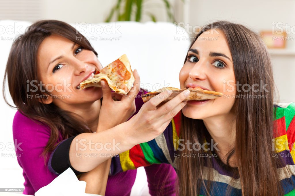 Two girls eating pizza together stock photo